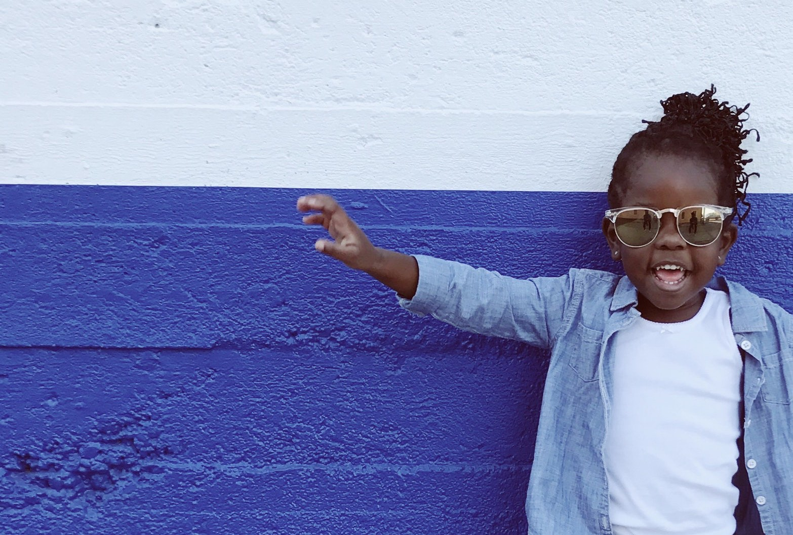 A child wearing a sun glasses is standing in front of a blue wall and smiling to the camera