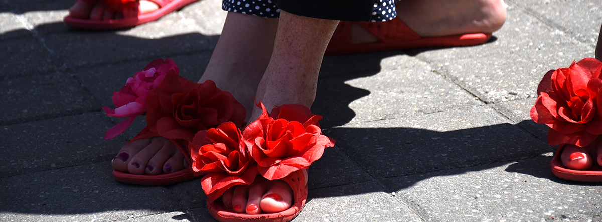A pairs of women's feet with red painted nails in a pair of red sandals that feature huge red flowers on the front.