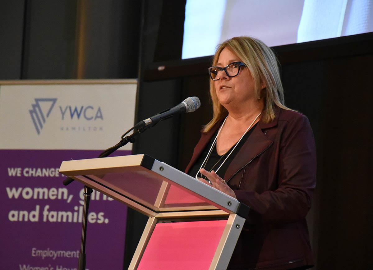 Denise speaking at a podium