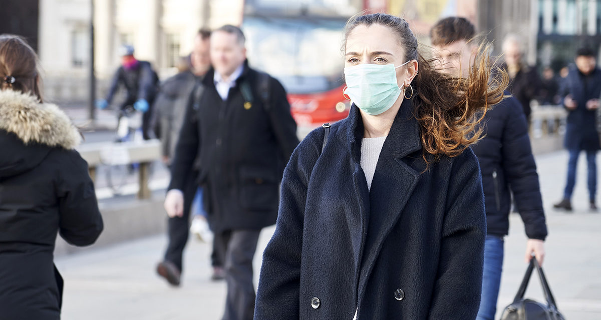 A woman wearing a face mask walks on a city street