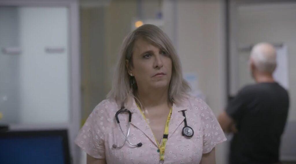A woman walks through a hospital hallway