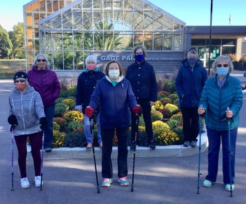 A group of women holding walking sticks and wearing masks stand slightly apart from each other.