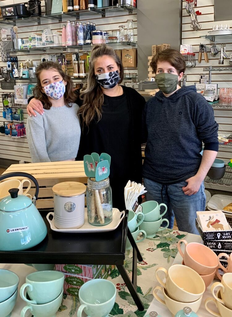 Three women wearing masks stand in the middle of a kitchen store.
