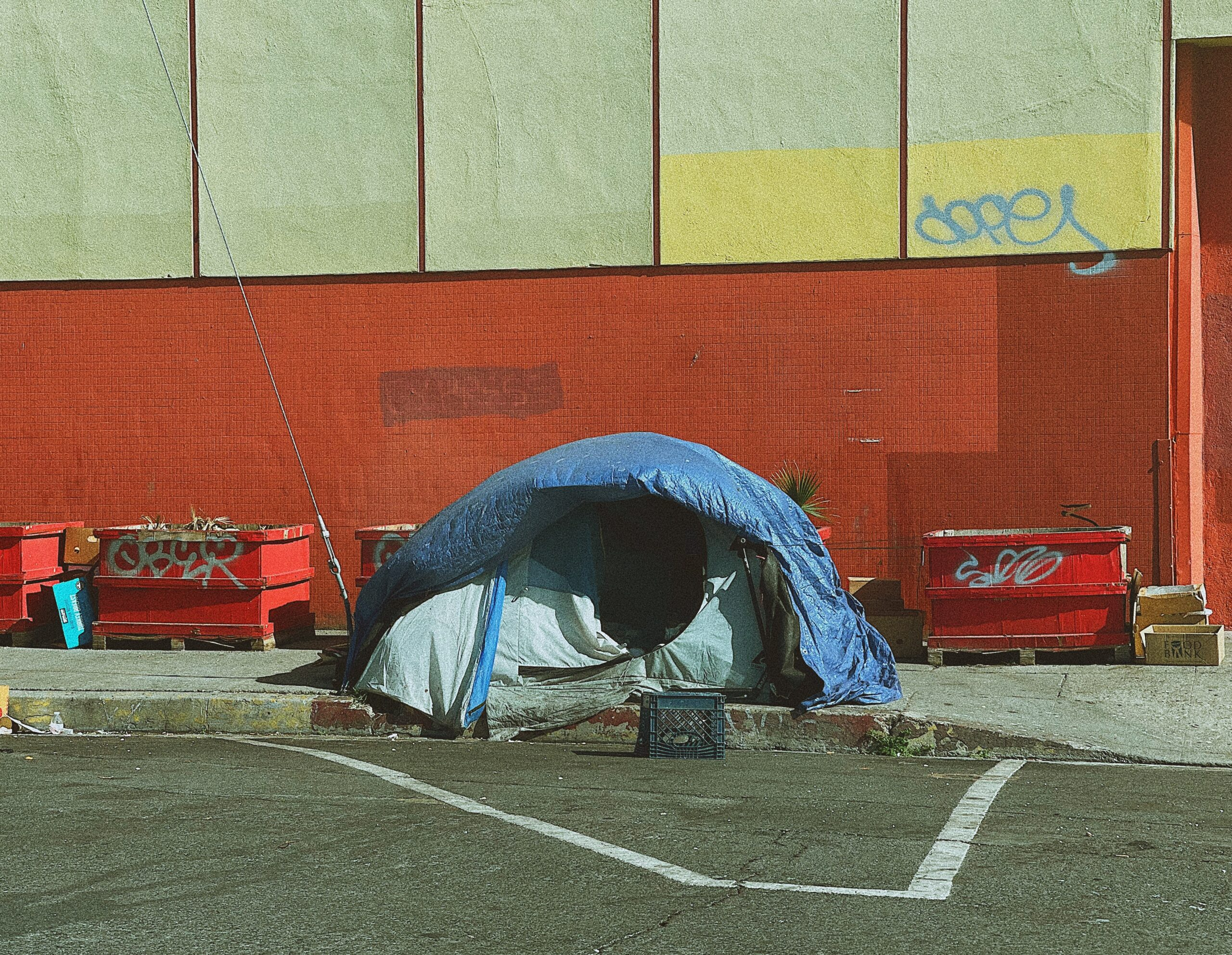 A camping tent set up on the sidewalk, photo by Naomi August on Unsplash