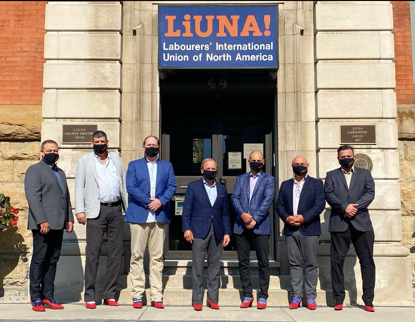 Joe Mancinelli and the crew from LiUNA (Labourers International Union of North America) wear red pumps in solidarity with survivors in front of the LiUNA offices.